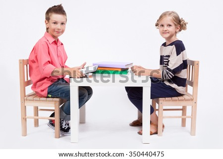 boy and girl sit at the table and draw on a white background