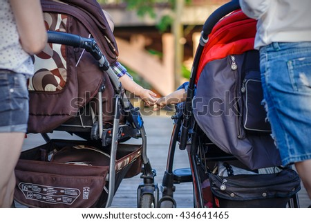 boy and girl sitting in baby carriages - stock photo
