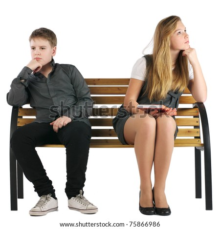 Boy and girl sitting on a bench and not looking at each other - stock photo