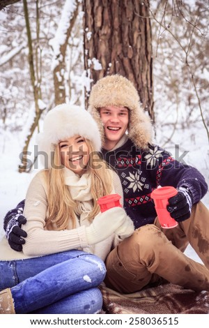 boy and girl sitting on a blanket, winter in the woods, smiling, holding red cup in his hands