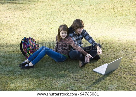 Boy and girl sitting on grass, online, pointing to the laptop screen