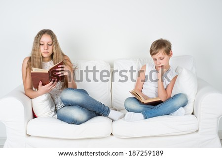 Boy and girl sitting on the couch and read a book