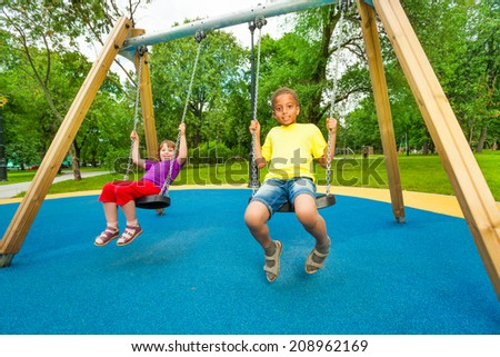 Boy and girl sitting on the swings together - stock photo