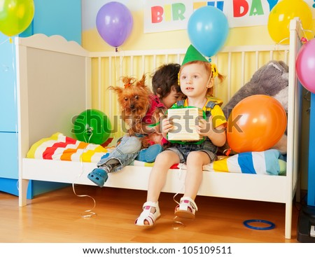 boy and girl sitting with dog and present at birthday party