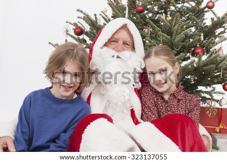 Boy and girl sitting with santa claus smiling, portrait