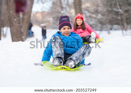 boy and girl sliding on sledges in park. two children sitting on sledges and speeding down - stock photo