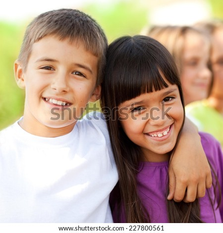 Boy and girl smiling in nature. Elementary age.