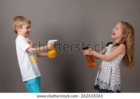 boy and girl squirting water and happy - stock photo