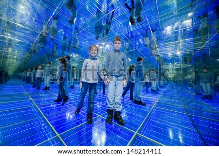 Boy and girl standing in a mirrored room with blue lights holding hands - stock photo
