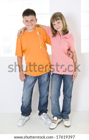 Boy and girl standing in front of window and listening to music by earphones. They hug each other. They smiling and looking at camera. - stock photo