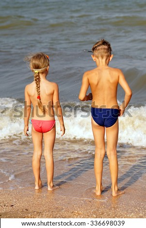 Boy and girl standing on the beach - stock photo