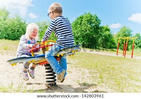 Boy and girl swinging on a swing - stock photo