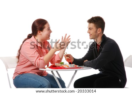 Boy and girl talking and eating sushi - stock photo
