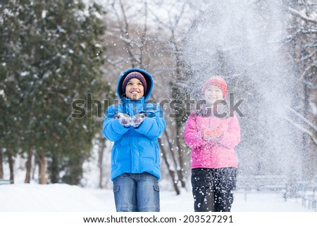 boy and girl throwing snow into air. two children playing in park and smiling - stock photo