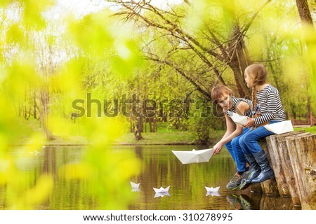 Boy and girl together near the pond play with paper boats on the water in beautiful forest landscape - stock photo