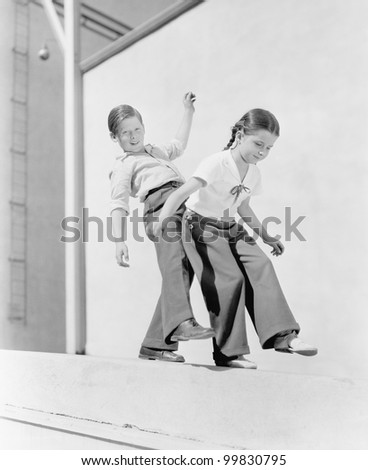 Boy and girl trying to balance on a ledge - stock photo