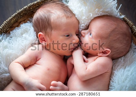 Boy and girl twins lying down together - stock photo