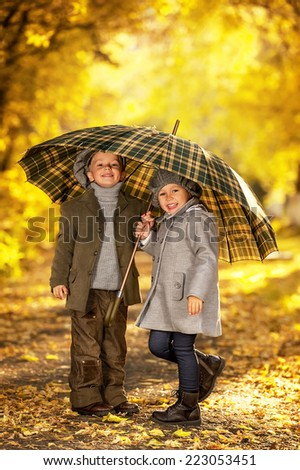 Boy and girl walk in autumn park on a warm sunny day - stock photo
