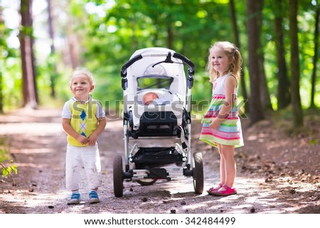 Boy and girl walk in sunny summer park pushing stroller with newborn sibling. Brother and sister playing with baby outdoors. Family with three kids walking in a forest. Group of little children. - stock photo