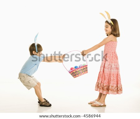 Boy and girl wearing bunny ears fighting over Easter basket. - stock photo