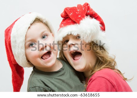 boy and girl, wearing Christmas hats and laughing - stock photo