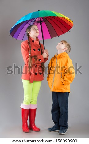Boy and girl with a colorful umbrella looking up, studio shot - stock photo