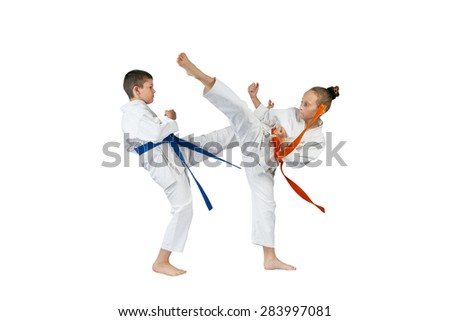 Boy and girl with different belts exchanged kicks - stock photo