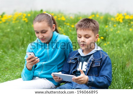 boy and girl with gadgets - stock photo