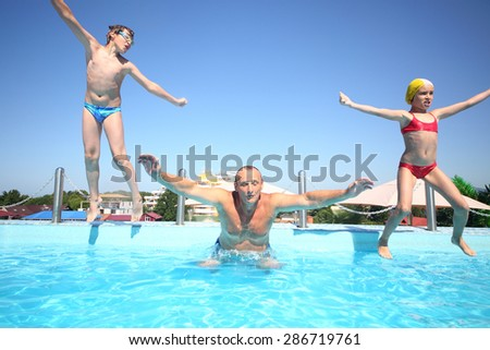 Boy and girl with grandfather jumping into a pool of water - stock photo