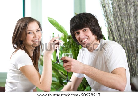 Boy and girl with smile with wineglasses - stock photo