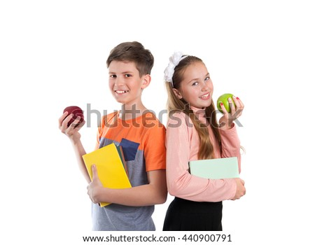 Boy and girl  with textbooks in hand are eating apples, isolated on white background - stock photo