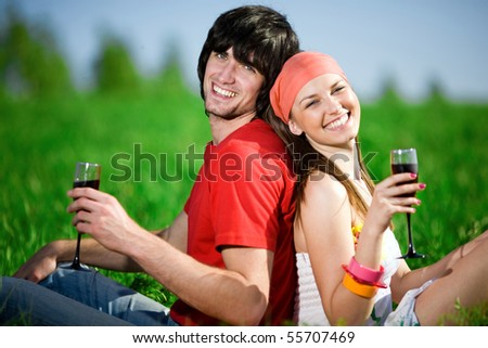 Boy and girl with wineglasses on grass - stock photo