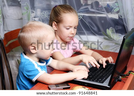 Boy and girl working together on a laptop - stock photo