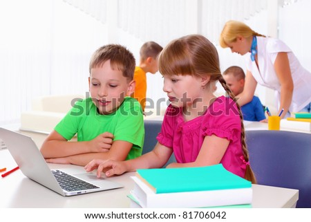 Boy and girl working together on a laptop at school.
