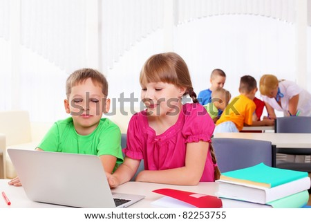 Boy and girl working together on a laptop at school. - stock photo