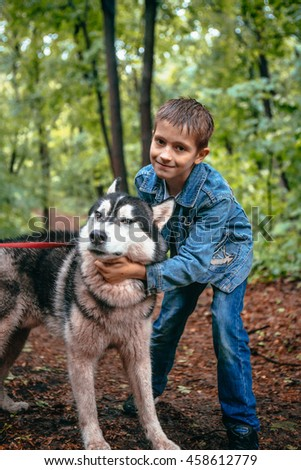 boy and his dog husky on the background of leaves in spring. - stock photo
