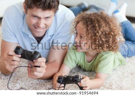 Boy and his father playing video games while lying on a carpet - stock photo