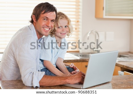 Boy and his father using a notebook together in a kitchen - stock photo