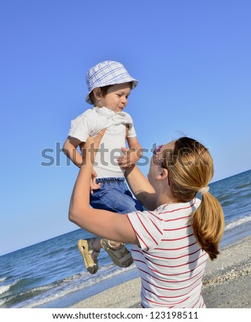 Boy and his mother at beach - stock photo