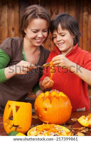 Boy and his mother having fun carving a jack-o-lantern for Halloween - stock photo