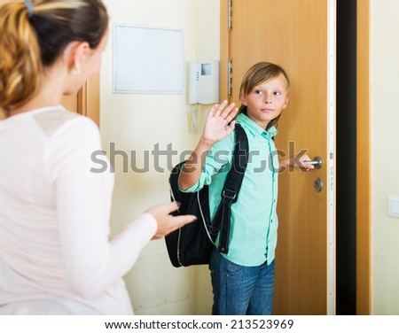 Boy and his mother staying near flat entrance and talking - stock photo