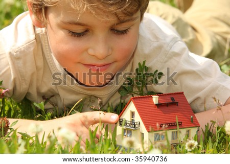 boy and house model in grass - stock photo
