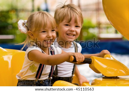 boy and little girl on attraction - stock photo