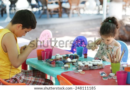 boy and little girl painting on white plaster - stock photo