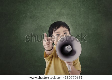 Boy and megaphone in front of blank board in class - stock photo
