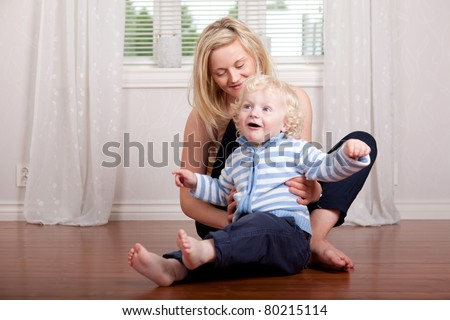 Boy and mother having fun at home