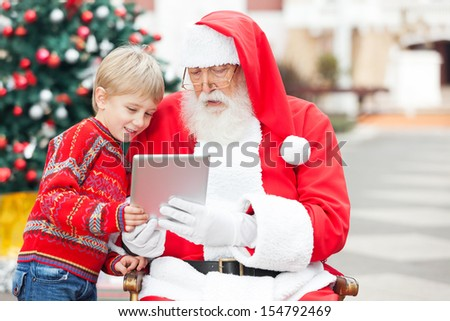 Boy and Santa Claus using digital tablet together in courtyard - stock photo