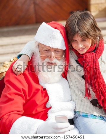 Boy and Santa Claus using smartphone together outside house - stock photo