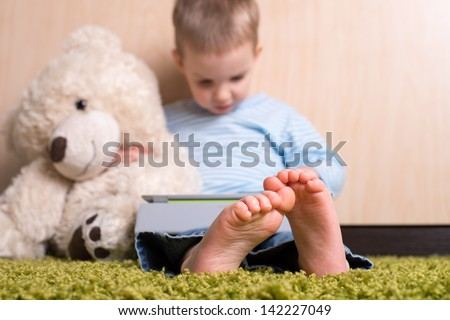 Boy and teddy bear with tablet computer, bare feet in focus - stock photo