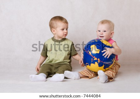 boy and the girl sit on a floor and play with ball